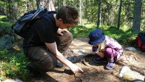 Niclas Fritzén sitter på huk i skogen och pekar på marken, hans dotter sitter mittemot och tittar där han pekar.