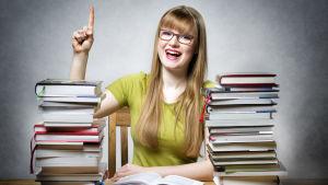 En glad kvinna med pekfingret utsträckt sitter bakom två högar av böcker.