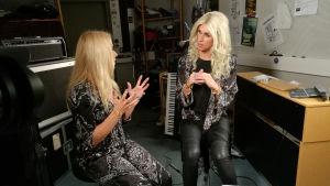 Krista och Christoffer sitter i en musikstudio och pratar med varandra. Christoffer är utklädd till Krista i blond peruk. Han härmar också hennes kroppsspråk.