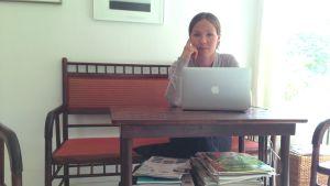Julia Korkman sitter vid ett bord med en dator framför sig