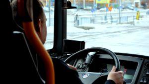 Busschaufför bakifrån vid ratt. Utsikt mot gata i Ekenäs.