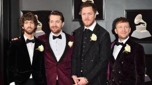 Musikgruppen Imagine Dragons poserar för bild klädda i kostym och en vit ros vid bröstet.
