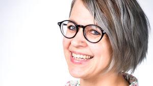 Halvbild på kvinna i blommig skjorta, svarta glasögon och pagefrisyr.