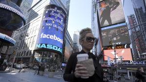 En ung dam med kaffemugg går på gatan i New York.