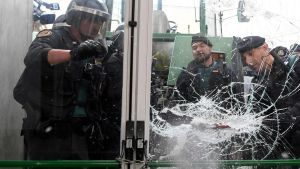 Kravallpolis slår sönder dörren till en vallokal i Katalonien.
