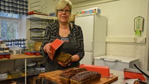 Kvinna stjälper upp bröd från formar.