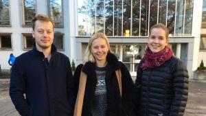 En manlig och två kvinnliga studerande utanför institutionen för nordiska språk vid Helsingfors universitet.