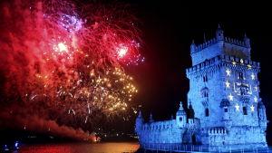 Belémtornet i Portugal upplyst med blått ljus, röda fyrverkerier i bakgrunden.