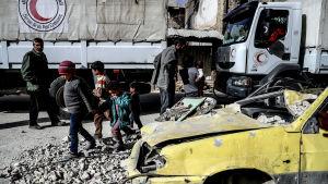 Människor intill hjälpkonvojen då den anlänt till Douma, i östra Ghouta.