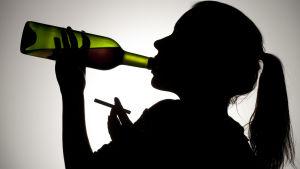 Ung kvinna dricker och röker.