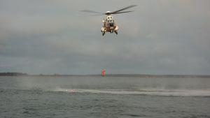 En yträddare hoppar i vattnet från Sjöbevakningens helikopter.