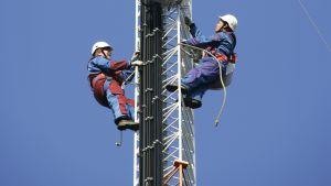 Två män i arbetskläder och hjälm klättrar upp i en mast.