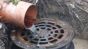 Vatten rinner ut i en avloppsbrunn