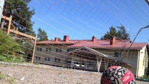 En boll på en sandplan. I bakgrunden ett fotbollsmål och en gul skolbyggnad.