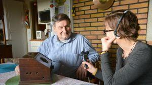 Henrik Dahl förevisar en av sina gamla apparater för Nilla Hansson