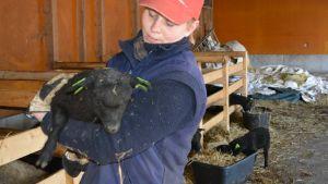 Crista Hällfors håller ett av familjens svarta lamm