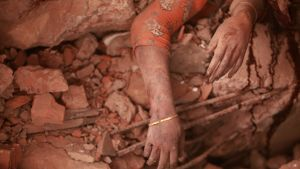 Nainen romahtaneen tehtaan raunioissa.
