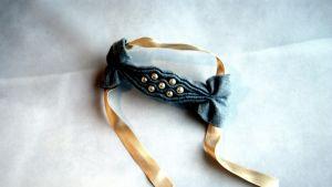 Ett pärlsmockat armband av grått filttyg med ljusgult sidenband.