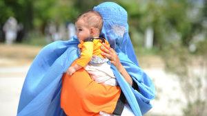 En afghansk kvinna iklädd blå burka bär på ett litet barn. Hon återvänder frivilligt från Pakistan till hemlandet.