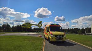 En läkarhelikopter landar invid en väntande ambulans.