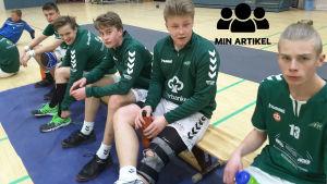 EIF-pojkar sitter på bänken före matchen.