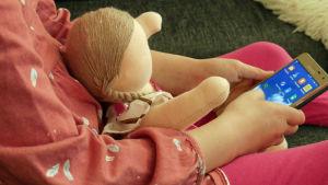 Lapsi istuu sohvalla älypuhelin kädessään ja nukke sylissään, värikorjattu