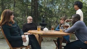 Chris (Daniel Kaluuya) sitter tillsammans med Rose (Allison Williams) och hennes familj vid ett altanbord och dricker ice tea.