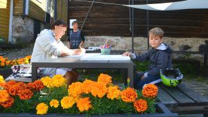 En äldre kvinna och en son sitter vid ett bord. Kvinnan tecknar. I förgrunden orange blommor, i bakgrunden en kvinna till.