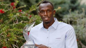 Usain Bolt håller i en pokal