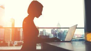 Sivukuva naisesta kannettavan tietokoneen äärellä. Vastavaloon. Takana kaupungin silhuettia.