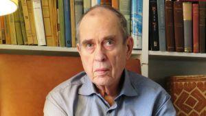 Författaren Jörn Donner sitter framför sin bokhylla