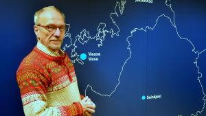 Nils Torvalds poserar framför en karta av Österbotten.