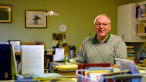 Robert Karlman står bakom en lägre bokhylla i sitt antikvariat.