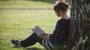 Nainen istuu nurmikolla, lukee kirjaa ja nojaa koivuun