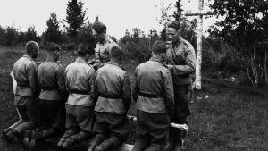 Sotilaspastorit jakamassa ehtoollista kentällä