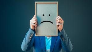 En man i kostym som skymmer sitt ansikte med en tavla föreställande ett ledset ansikte.