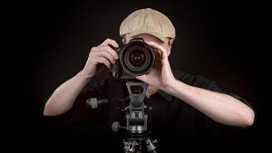 Man som står bakom en kamera