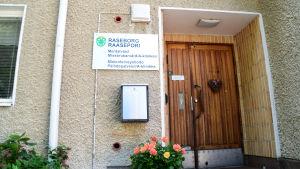 En bild på en dörr på ett hus. En blomma står på trappan och ett hjärta hänger på dörren. På en skylt står det Raseborgs Mentalvård, Missbrukarvård/A-kliniken på finska och svenska.