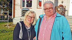Sirpa och John Mannil framför sitt hus i Vörå