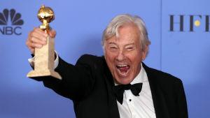 """Paul Verhoeven, regissör för den franska filmen """"Elle"""" håller upp sin Golden Globe-statyett 8.1.2017"""