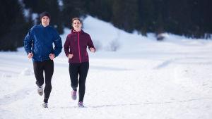 Två personer som ser glada ut, ute på en löprunda i snöigt landskap.