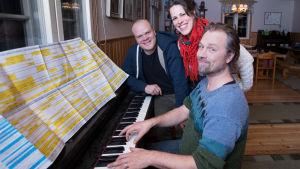 Tre personer vid ett piano
