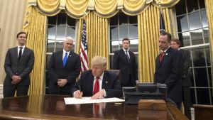 Trump undertecknar sitt första presidentdekret i Ovala rummet.