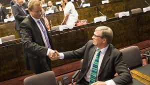 Antti Kaikkonen (stående) gratuleras av sin motkandidat Timo Kalli.