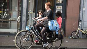 En kvinna och ett barn cyklar. Ett mindre barn sitter på pakethållaren.
