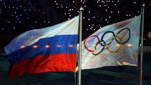 Den ryska flaggan svajar bredvid den olympiska flaggan.