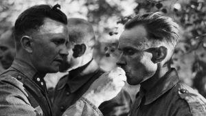 Sotilaspastori jakamassa ehtoollista kentällä