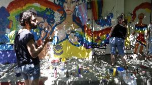 Deltagare i årets pridefestival i Istanbul målar regnbågens färger på en vägg under ett evenemang.