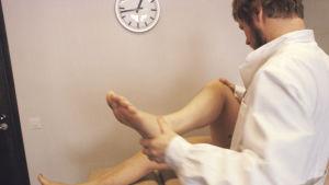 En läkare undersöker rörligheten i knät hos en patient