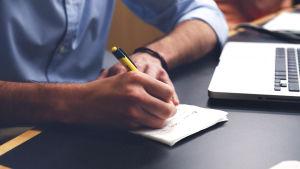 En man skriver på ett papper.